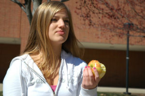 SLIMMING DOWN: Junior Megan Bournique eats an apple. Bournique works out at least four times a week and maintains a healthy diet not only to get in shape for spring break, but also to make herself feel confident. ARJUNA CAPULONG / PHOTO