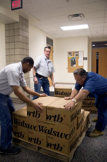 HOT OFF THE PRESS: Carmel High School custodial workers load 2008-09 yearbooks onto crates for distribution. Students may begin picking their orders up next Monday. MICHELLE HU / PHOTO